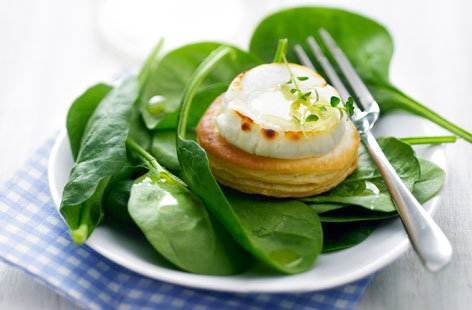 187422 goat's cheese and honey mini puff pastry tarlets with baby spinach leaves HERO