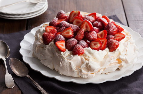 Tuck into this deliciously crisp Pavlova topped with whipped cream and juicy strawberries