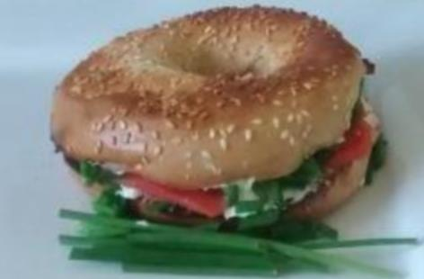 Toasted sesame seed bagel containing smoked salmon, soft cheese and chives