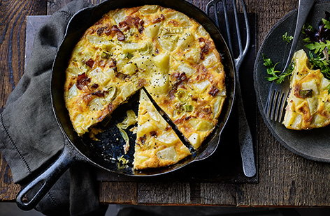 This quick frittata recipe is perfect when there's not much in the fridge. Crispy bacon, sweet leeks and tender potatoes are cooked with eggs and a generous amount of cheese for an easy dinner idea or weekend lunch - pack the leftovers into lunchboxes.