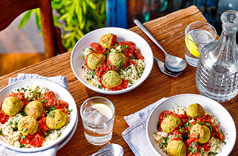 A fan of falafel? Make this hearty falafel traybake recipe for a comforting vegan dinner idea. Homemade falafel are quick to blitz together, before being baked in tomato sauce and served with herby lemon couscous.