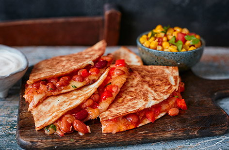 Serve up a Mexican feast with this vegetarian bean quesadillas recipe. Fry tortillas filled with spicy taco beans, BBQ sauce, peppers and plenty of melting cheese, then spoon over a quick sweetcorn salsa and a dollop of cooling soured cream.