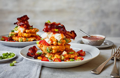 Turn brunch into dinner with this sweetcorn fritters recipe. Top a stack of fluffy sweetcorn fritters with crispy bacon, a dollop of créme fraîche, a scattering of spring onions and a drizzle of fiery sriracha sauce for a meal that works at any time of day