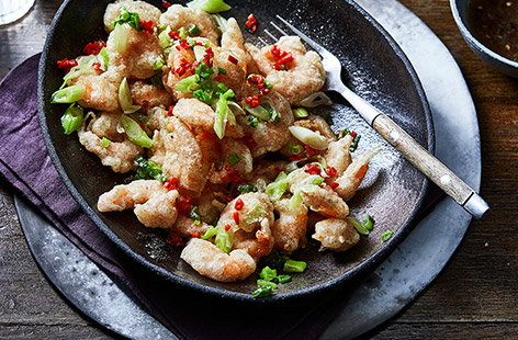 Try our easy spin on the takeaway favourite of salt and pepper prawns. Coat the jumbo king prawns in a crispy seasoned batter and scattered with fresh spring onion and fiery red chilli.