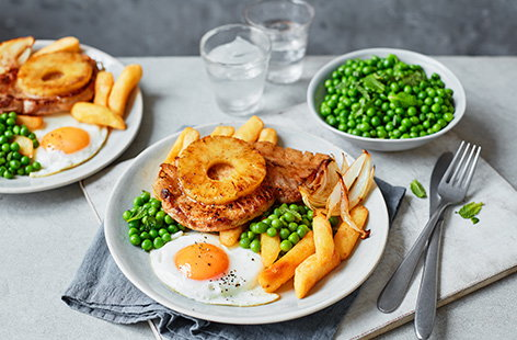 We've updated a pub classic with this pork, egg and chips recipe. Top tender pork loin steaks with juicy caramelised pineapple and a perfectly fried egg, then serve with peas and crispy chips for a simple family favourite.