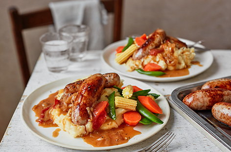 Sausages and mash is a comfort food classic. We've taken it up a notch here by adding a homemade tomato and onion gravy recipe and grating Cheddar into the potatoes for an extra indulgent cheesy mash.