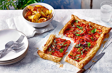 Make this simple tomato galette recipe for an easy summer dinner. Perfect if you've bought or grown too many tomatoes, this easy bake is served with homemade potato wedges for a new vegan dinner idea.