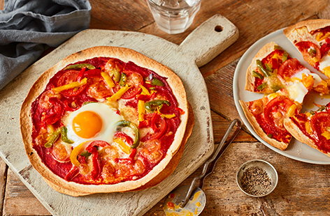 Have homemade pizzas in just 15 minutes with this easy tortilla pizzas recipe. Stack tortilla wraps for a super crunchy cheat's pizza base, then top with your favourite toppings - we've used peppers, tomatoes, melting mozzarella and cracked an egg on top!