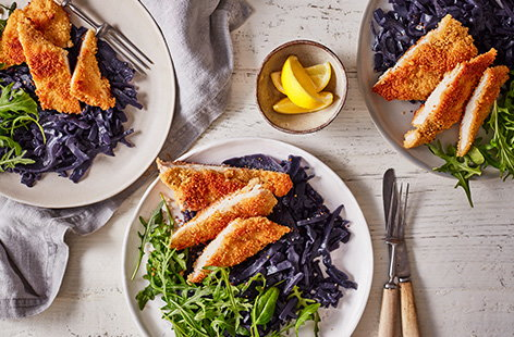 For dinner ready in 30 mins, try this couscous chicken schnitzel. Using couscous for an easy crispy coating, serve with braised red cabbage and rocket for a quick and healthy midweek dinner.