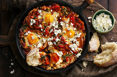 Warm chilli and tomato sauce meets peppers, spinach and feta in this lazy baked eggs dish, which takes just 20 minutes to make