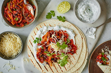 Go Mexican for dinner tonight with this veggie bean fajita recipe. Make a smoky paprika-spiced black bean mixture with peppers and onions, then let everyone load up their own tortillas and top with cheese, yogurt and coriander.