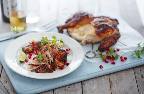 Want to cook a whole chicken on the BBQ? Spatchcocking it will help it cook quickly and evenly, keeping it tender but with delicious smoky charred skin. We've given it a Middle Eastern-style twist with spiced yogurt and pomegranate seeds.