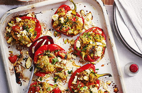Load up peppers with the stuffing, tomatoes, rice and spring onions and finish with parsley and crumbly Greek salad cheese.