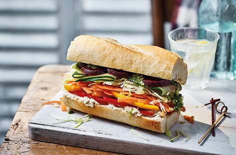 Put some colour into lunch with this vibrant veg-packed baguette that's bursting with fresh ingredients. Creamy houmous and punchy pesto add a boost of flavour while the layered veg create different textures and fun rainbow effect for a healthy lunch.