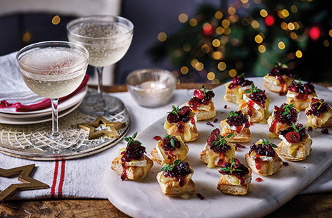 Combine classic festive flavours in this simple canapé recipe. A tangy homemade cranberry sauce and gooey, melting Camembert are layered on top of crisp puff pastry, perfect for Christmas parties.