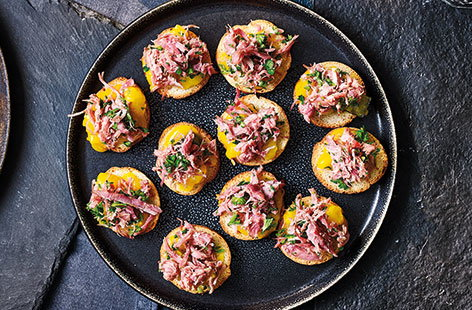 Serve up simple Christmas canapés that layer crostini with mustard piccalilli and zesty, herby ham hock