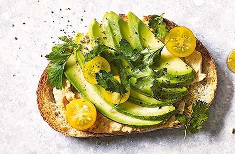 Houmous, avocado and yellow tomatoes toast topper