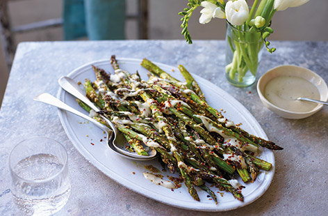 Make the most of seasonal British asparagus with this easy side dish. Delicate asparagus stems are simply roasted with a garlic and soy marinade and sesame seeds for a nutty crunch – delicious on its own or drizzled with the creamy tahini dressing.