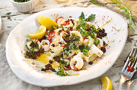 This sticky garlic squid is an ideal easy sharing starter, ready in just 15 minutes. Squid is stir-fried in garlic and chilli until sticky and caramelised, then topped with crispy capers for a simple finishing flourish. Serve with plenty of fresh lemon.