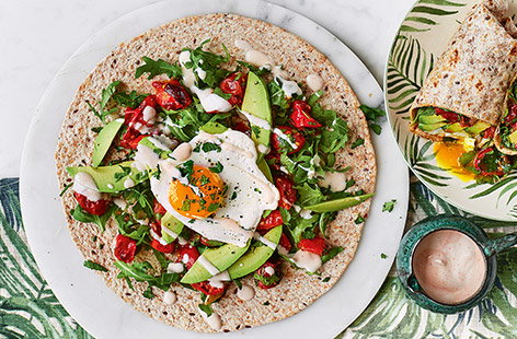 Start the day with this hearty breakfast that will keep you full all morning. This breakfast burrito combines fried eggs, roasted tomatoes and spicy sriracha yoghurt – add bacon to make it even more substantial.