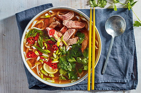 This Vietnamese-inspired quick beef pho is a speedy midweek meal that can be made in under 30 minutes. Freezing the steak makes it easy to slice very thinly, which helps it cook quickly in the spiced broth for perfectly tender results.