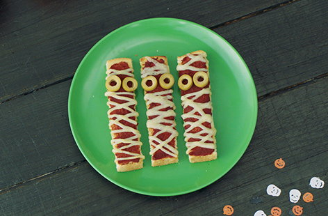 Serve up a spooky snack for Halloween with these fun, gross toasts. Made to look like bandaged mummies, these toast fingers are topped with cheese and tomato for a pizza-like flavour that the kids will love.