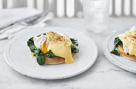Perfectly poached eggs, silky spinach and creamy hollandaise sit atop toasted muffins in this indulgent brunch recipe