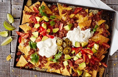 Perfect for sharing, these easy nachos with salsa and refried beans are great for a party or a night in watching a film