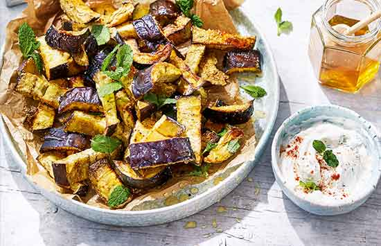Baked aubergine 'chips' make a moreish easy starter or side dish. Chunky wedges of aubergine are coated in polenta for maximum crunch and baked until crisp, plus a sweet drizzle of honey helps them caramelise in the oven.