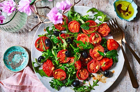Slow-roasting results in sweet, sticky, intensely flavoured tomatoes that are delicious in this punchy Mediterranean salad of rocket, olive, capers and pine nuts. This technique is also handy if you're hosting a crowd as there's very little hands-on effort