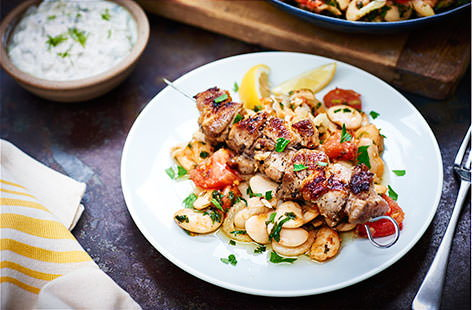 Rustle up some authentic Greek souvlaki for the ultimate fakeaway. Succulent pork belly is marinated in lemon, oregano, bay leaf and garlic, served with fragrant butter beans and creamy tzatziki.