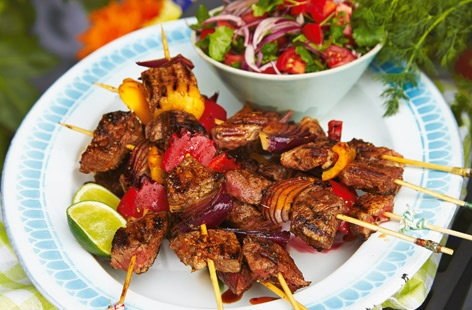 Brazilian-style barbecue beef skewers with tomato salad